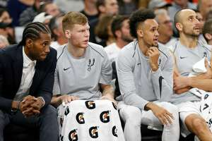 San Antonio Spurs' Kawhi Leonard (from left), Davis Bertans, Derrick White, and Manu Ginobili watch second half action against the Toronto Raptors from the bench Monday Oct. 23, 2017 at the AT&T Center. The Spurs won 101-97.