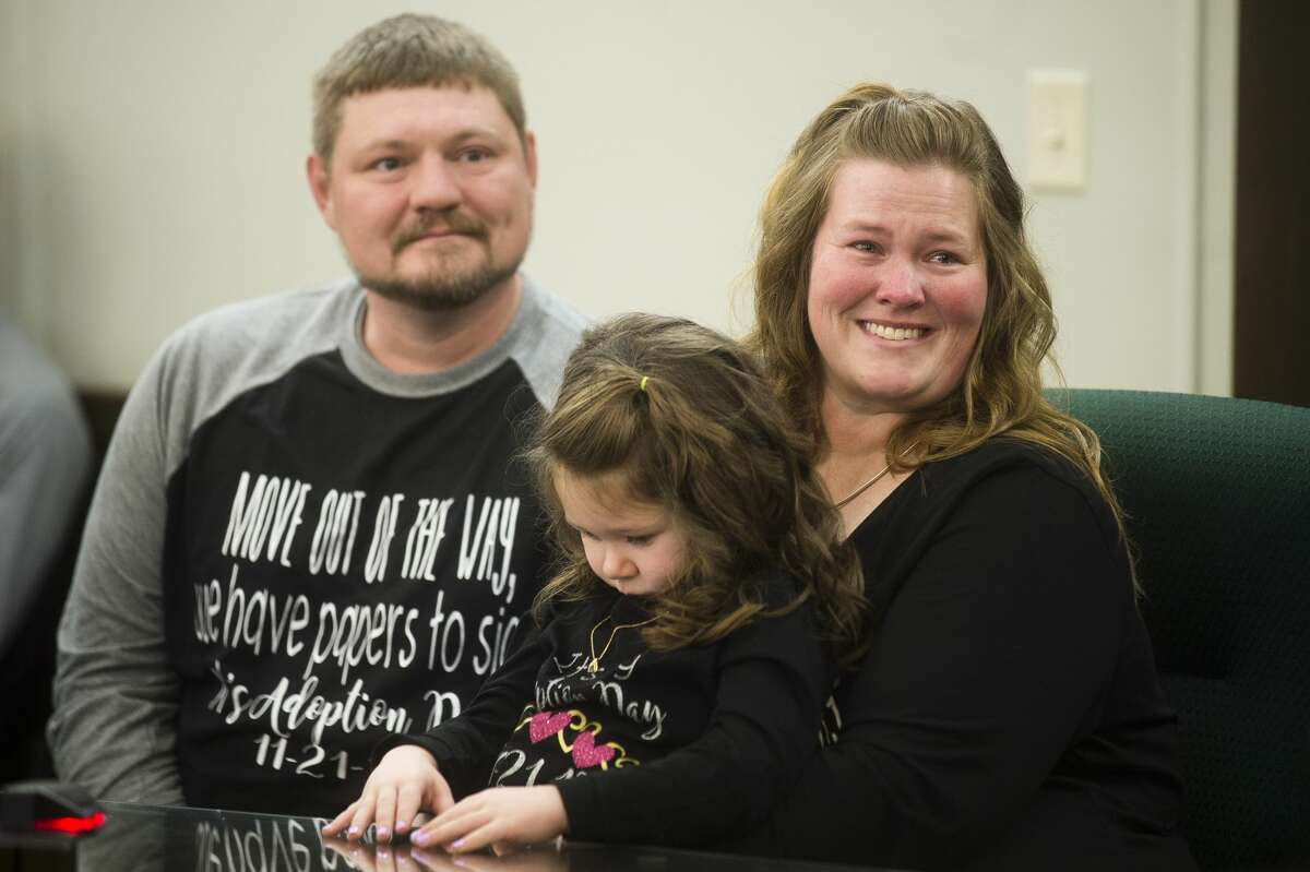 Chris Baker, left, Amanda Baker, right, and Adriana Baker, 4, center, listen to Midland County Probate and Family Court Judge Dorene S. Allen before Adriana's adoption is finalized during Adoption Day on Tuesday, Nov. 21, 2017 at the Midland County Courthouse. (Katy Kildee/kkildee@mdn.net)