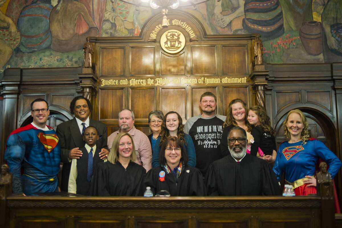 Three families pose for a photo with Michigan Supreme Court Justice Elizabeth T. Clement, center left, Midland County Probate and Family Court Judge Dorene S. Allen, center, and Michigan Supreme Court Justice Kurtis T. Wilder, center right, during Adoption Day on Tuesday, Nov. 21, 2017 at the Midland County Courthouse. (Katy Kildee/kkildee@mdn.net)