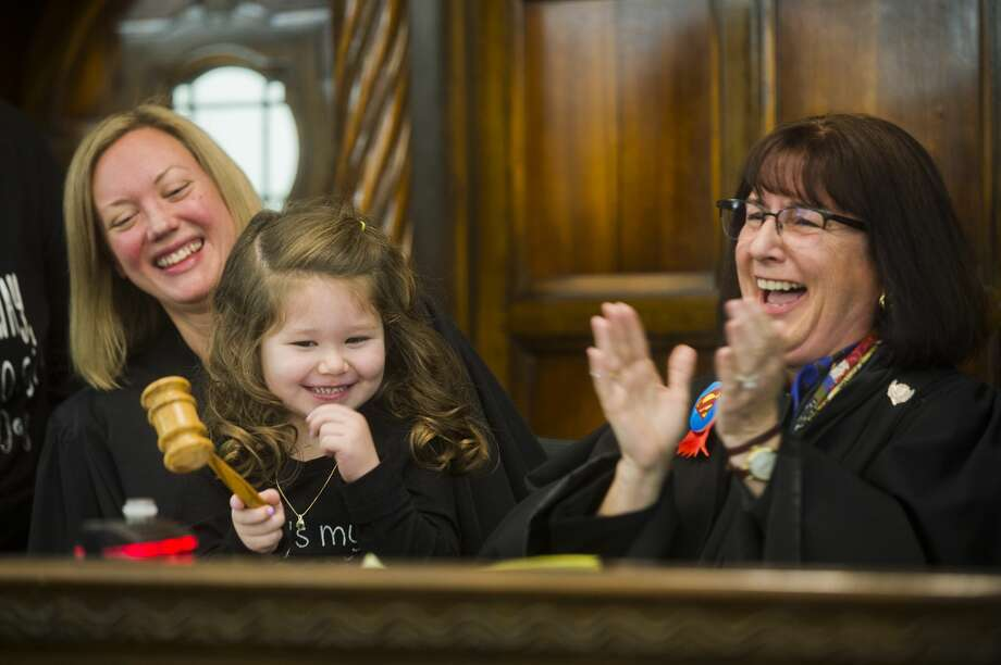 Adriana Baker, 4, adjourns her adoption proceeding on by pounding the gavel alongside Midland County Probate and Family Court Judge Dorene S. Allen, right, and Michigan Supreme Court Justice Elizabeth T. Clement, left, during Adoption Day on Tuesday, Nov. 21, 2017 at the Midland County Courthouse. (Katy Kildee/kkildee@mdn.net) Photo: (Katy Kildee/kkildee@mdn.net)
