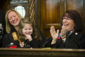 Adriana Baker, 4, adjourns her adoption proceeding on by pounding the gavel alongside Midland County Probate and Family Court Judge Dorene S. Allen, right, and Michigan Supreme Court Justice Elizabeth T. Clement, left, during Adoption Day on Tuesday, Nov. 21, 2017 at the Midland County Courthouse. (Katy Kildee/kkildee@mdn.net)