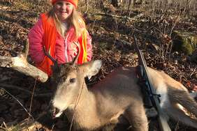 Lexie Harris, 6, poses after bagging a buck in Taylor County, Wis. Lexie is among the first youngsters to bag a buck under the state's new law that eliminates the state's minimum hunting age.