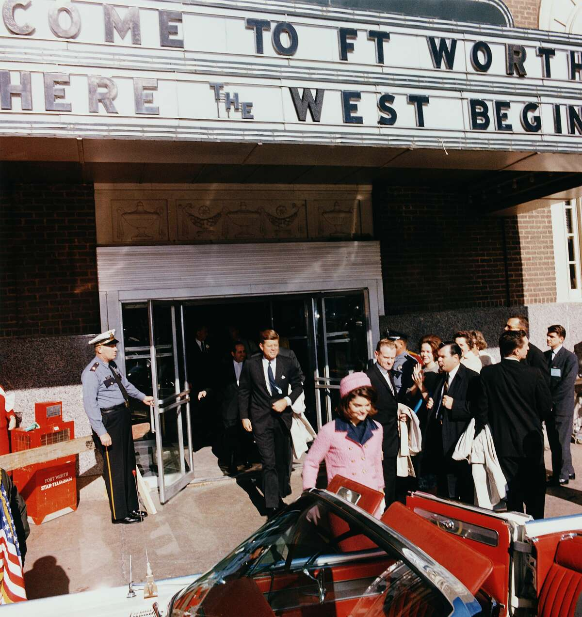 President John F. Kennedy and First Lady Jacqueline Kennedy emerge from a Fort Worth, Texas, theater, into a waiting car on the day of Kennedy's assassination, November 22, 1963.