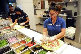 Emily Rea makes a customized pizza while working inside Pieology Pizzeria in Stamford Town Center's restaurant row in downtown Stamford, Conn. on Monday, Nov. 20, 2017.