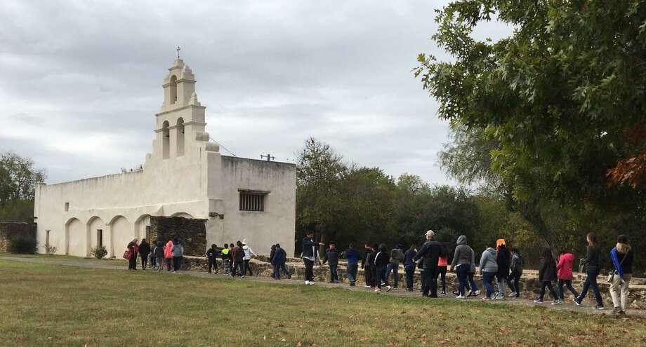 Students from Mary Hull Elementary School walk toward the church at Mission San Juan during a recent school field trip provided through the San Antonio Conservation Society's Heritage Education Tours program. Photo: Scott Huddleston / San Antonio Express-News