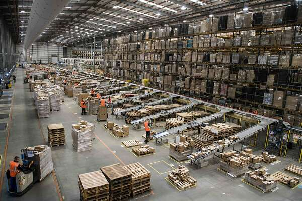 "Workers prepare customer orders for dispatch as they work around goods stored inside an Amazon.co.uk fulfillment centre in Peterborough, central England, on November 15, 2017. Shops could be seeing the effect of consumers postponing purchases until ""Black Friday"" on November 24, 2017, a day of sales in the United States that has become increasingly popular in Britain. / AFP PHOTO / CHRIS J RATCLIFFECHRIS J RATCLIFFE/AFP/Getty Images"