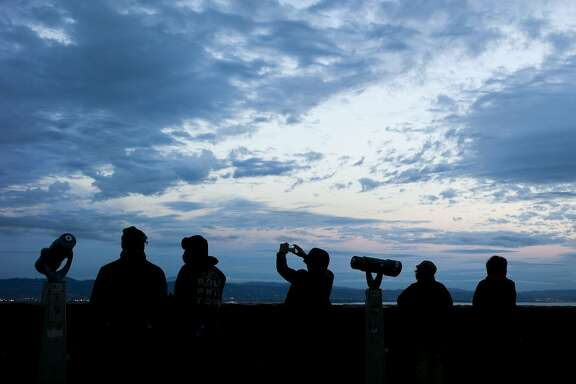 At Twin Peaks, people take photos as the weather worsens, Wednesday, Nov. 15, 2017, in San Francisco, Calif.