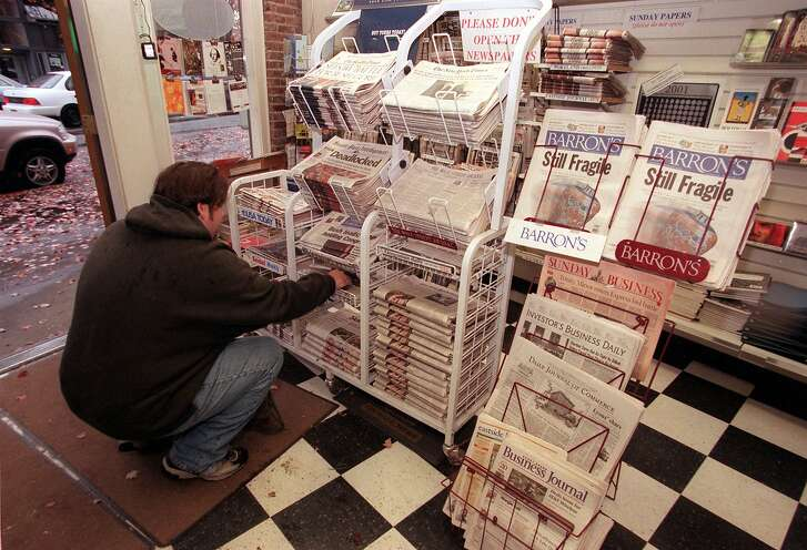 Adam Beales buys a newspaper at  Steves News in Fremont. Newspaper sales rack