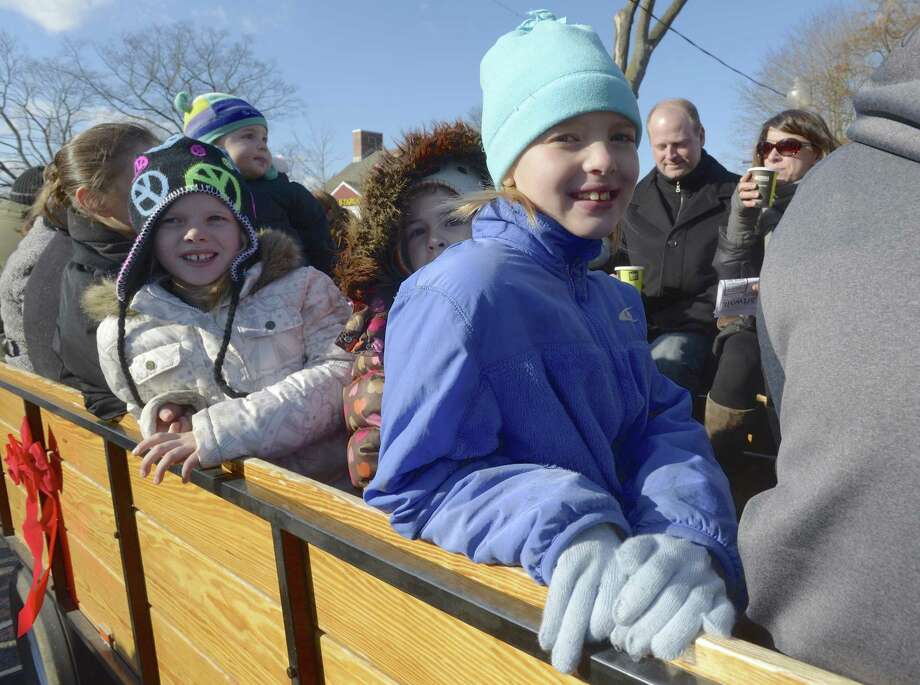 Rye Trask, 8, of Bethel, on right, Maya Raslan, 6, of Newtown, and Dylann Trask,8, left, of Bethel, get ready to go on a horse drawn carriage ride, part of Bethel WinterFest, in Bethel, Conn, on Friday November 29, 2013. The rides were  sponsored by Union Savings Bank. Photo: H John Voorhees III / H John Voorhees III / The News-Times Freelance