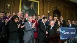 Are corporations people? If so, they will be very happy people under GOP tax plans. Rep. Kevin Brady (R-Texas) and House Speaker Paul Ryan (R-Wis.), center, shake hands during a news conference with other House Republicans, at the Capitol after the House passed a sweeping rewrite of the tax code on Nov. 16.