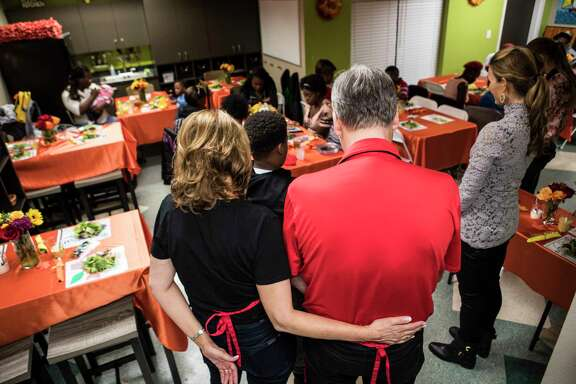 Eric Douglas, 11, leads a prayer while standing in front of Rockets coach Mike D'Antoni and his wife, Laurel, during a Thanksgiving meal served by the team's coaching staff on Monday night.