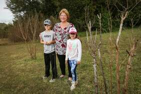 April Sound resident Dona Davis is pictured with two of her grandchildren between two crepe myrtle trees in a public space near her home on Tuesday, Nov. 21, 2017.