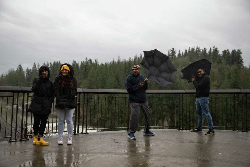 Spectators hold onto their umbrellas as the wind howls at Snoqualmie Falls on Tuesday, Nov. 21, 2017.