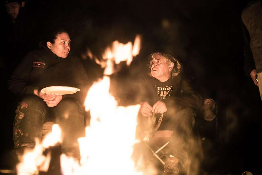Hillary Renick (left) and Eddie Knight Sr. sit around a fire with others at Renick's house.