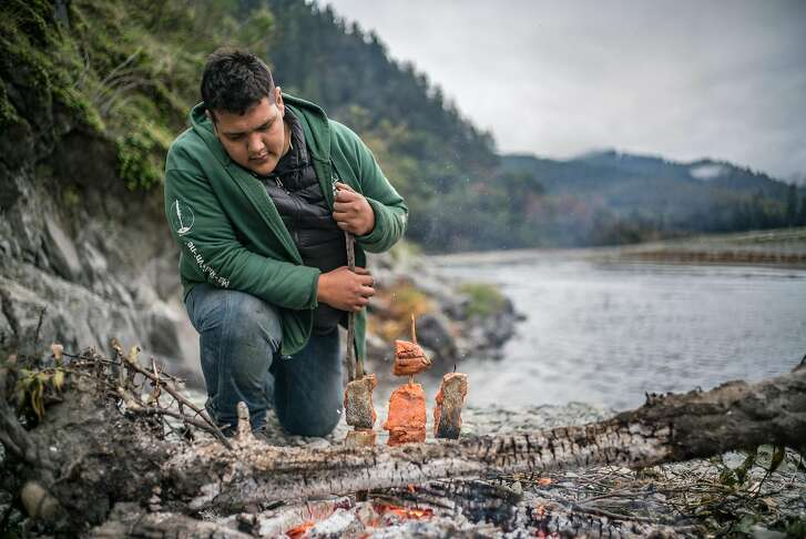 Sammy Gensaw prepares salmon filets next to the Klamath River on the Yurok Reservation on Thursday, Nov. 2, 2017.