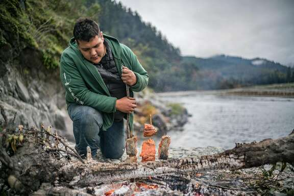 Sammy Gensaw prepares salmon filets next to the Klamath River on the Yurok Reservation on Thursday, Nov. 2, 2017.
