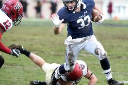 Zane Dudek (right) of Yale runs the ball against Harvard in the second quarter at the Yale Bowl in New Haven on November 18, 2017.