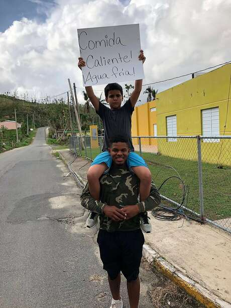 """Giants prospect Heliot Ramos in Matuyas Alto, Puerto Rico, after Hurricane Maria. The boy is Willie Joe Ronda, the son of Ramos' lead agent. His sign reads, """"Hot food! Cold water!"""" Photo: Heliot Ramos"""