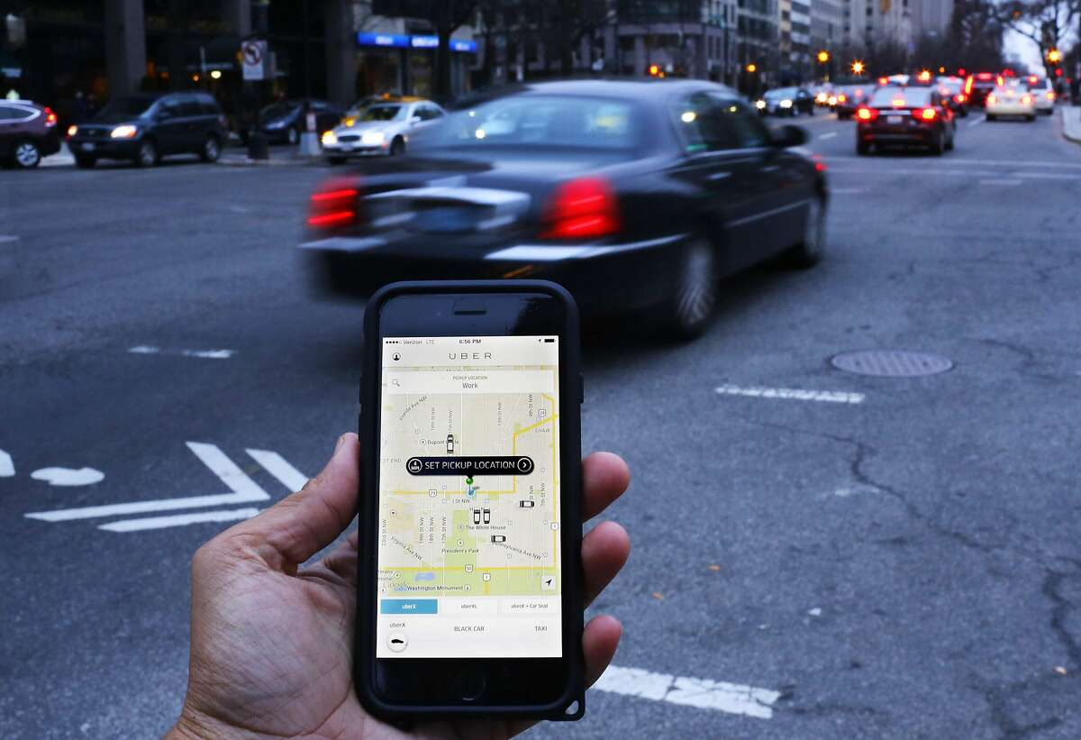 (FILES) This file photo taken on March 25, 2015 shows an UBER application shown as cars drive by in Washington, DC. A driverless, electric car is only a swipe away in the cities of the future, where pollution clampdowns and rapid advances in technology will transform the way we travel, despite lagging infrastructure. As more and more countries announce a phasing-out of pure petrol and diesel cars, early versions of tomorrow's models are already on the streets: hybrid cars, fully electric motors and vehicles that can partially drive themselves. / AFP PHOTO / Andrew Caballero-ReynoldsANDREW CABALLERO-REYNOLDS/AFP/Getty Images