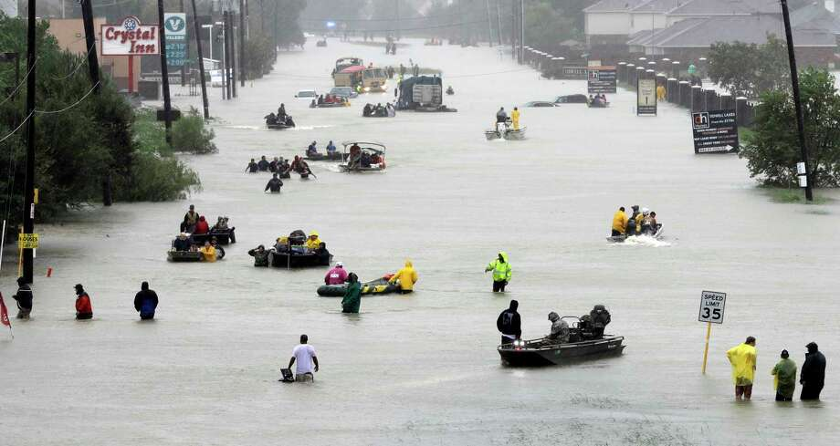 Rescue boats fill a flooded street as flood victims are evacuated as floodwaters from Tropical Storm Harvey rise in Houston on Aug. 28, 217.  (AP Photo/David J. Phillip File) Photo: David J. Phillip, STF / Copyright 2017 The Associated Press. All rights reserved.