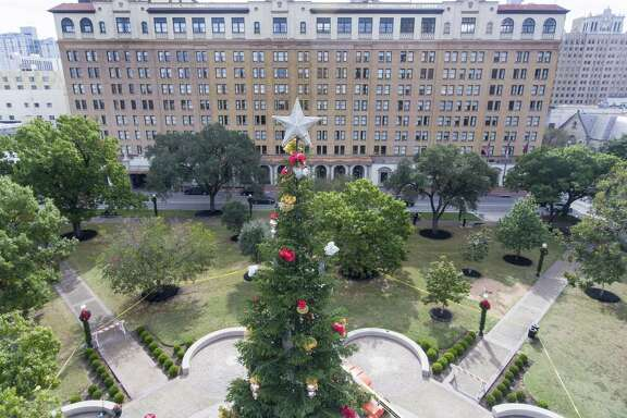The 55-foot San Antonio Christmas tree stands Tuesday, Nov. 21, 2017 in the middle of Travis Park, with the St. Anthony hotel in the background. The holiday tree was moved to Travis Park from Alamo Plaza after the Confederate soldier monument was removed from the park and in anticipation of changes coming to Alamo Plaza with proposed redevelopment of the area.
