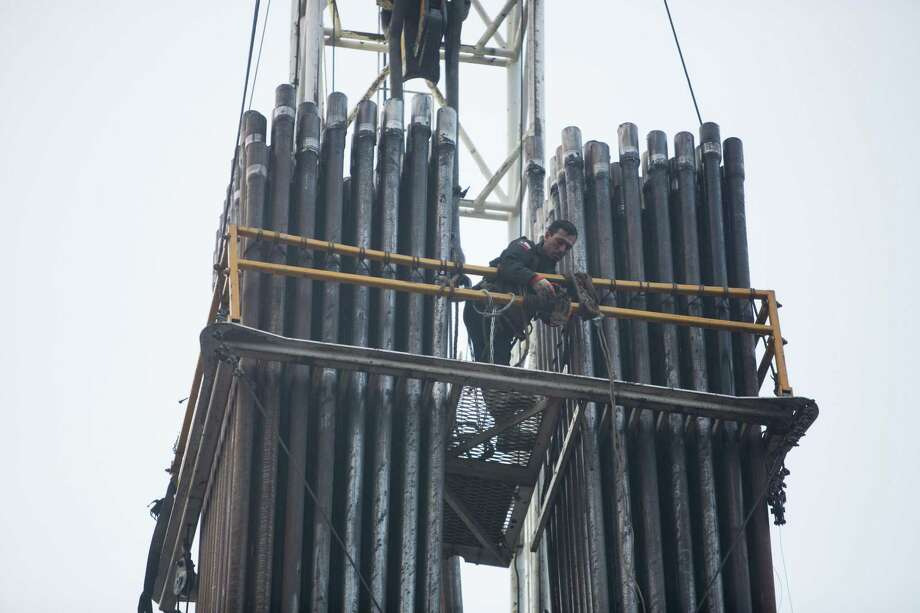 An oil field worker posiitons himself in the derrick position on an oil rig in Hallettsville, Texas on May 22, 2015. The drill collars stand next ti him. Photo: Carolyn Van Houten, Staff / San Antonio Express-News / San Antonio Express-News