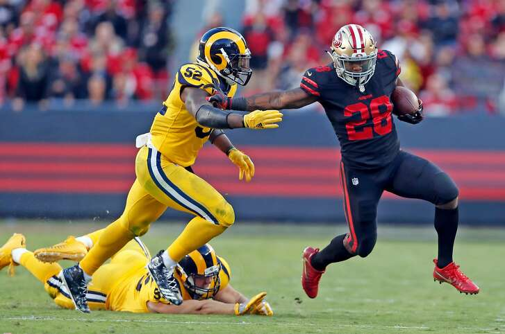 San Francisco 49ers' Carlos Hyde tries to stiff arm Los Angeles Rams' Alec Ogletree in 2nd quarter during NFL game at Levi's Stadium in Santa Clara, Calif., on Thursday, September 21, 2017.