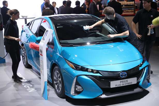 FRANKFURT AM MAIN, GERMANY - SEPTEMBER 12:  Workers prepare a Toyota Prius plug-in hybrid at the 2017 Frankfurt Auto Show on September 12, 2017 in Frankfurt am Main, Germany. The Frankfurt Auto Show is taking place during a turbulent period for the auto industry. Leading companies have been rocked by the self-inflicted diesel emissions scandal. At the same time the industry is on the verge of a new era as automakers commit themselves more and more to a future that will one day be dominated by electric cars.  (Photo by Sean Gallup/Getty Images)