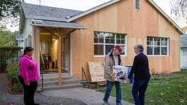 From left: Michelle Hickman takes a step aside as her in-laws Jim and Donna Hickman help her move into her new home on Friday, Nov. 17, 2017, in Calistoga, Calif. Michelle Hickman and their family were burned out of their rental home by the Tubbs Fire. The Chronicle's Season of Sharing helped them rent a new place in Calistoga.