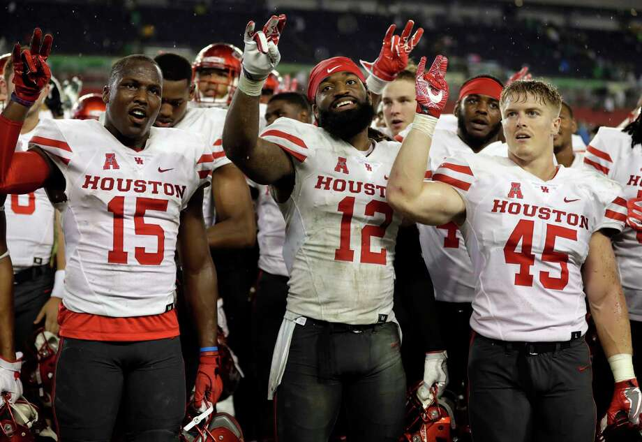 Houston players, from left, wide receiver Linell Bonner (15), linebacker D'Juan Hines (12) and linebacker Cameron Doubenmier (45) celebrate after the team defeated South Florida 28-24 during an NCAA college football game, Saturday, Oct. 28, 2017, in Tampa, Fla. (AP Photo/Chris O'Meara) Photo: Chris O'Meara, STF / Copyright 2017 The Associated Press. All rights reserved.