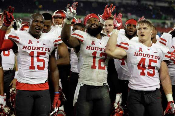 Houston players, from left, wide receiver Linell Bonner (15), linebacker D'Juan Hines (12) and linebacker Cameron Doubenmier (45) celebrate after the team defeated South Florida 28-24 during an NCAA college football game, Saturday, Oct. 28, 2017, in Tampa, Fla. (AP Photo/Chris O'Meara)