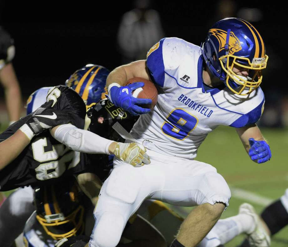 Brookfield's Connor McVey (9)  runs through the line as Barlow's Henry Eubanks (36) reaches out in the football game between Brookfield and Joel Barlow high schools, Friday night, October 27, 2017, at Joel Barlow High School, in Redding, Conn. Photo: H John Voorhees III / Hearst Connecticut Media / The News-Times