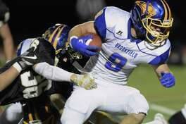 Brookfield's Connor McVey (9)  runs through the line as Barlow's Henry Eubanks (36) reaches out in the football game between Brookfield and Joel Barlow high schools, Friday night, October 27, 2017, at Joel Barlow High School, in Redding, Conn.