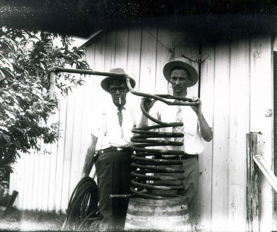 San Antonio Police Department detectives Vogler and Littlepage hold the coils of an elaborate distillation apparatus that they seized in a raid at a house located on Guenther Street in 1927. Photo: Courtesy UTSA Special Collections / San Antonio Light Collection