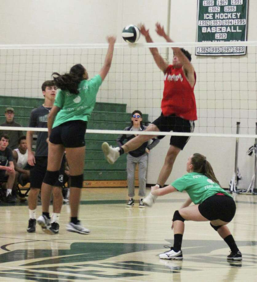 New Milford High School recently offered a special event with two of its sports teams. The NMHS girls volleyball team and the NMHS football took to the court for a volleyball game. The girls won the first match, followed by a win from the boys and another win by the girls. Above, junior Hunter Skelly tries to block a spike from senior Sunita Pfitzner. Photo: Courtesy Of Katie Alzapiedi / The News-Times Contributed