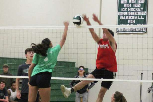New Milford High School recently offered a special event with two of its sports teams. The NMHS girls volleyball team and the NMHS football took to the court for a volleyball game. The girls won the first match, followed by a win from the boys and another win by the girls. Above, junior Hunter Skelly tries to block a spike from senior Sunita Pfitzner.