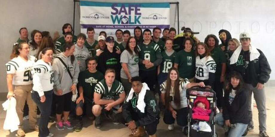 Members of the New Milford High School football team, along with their parents, recently participated in the Women's Center of Greater Danbury's annual Safe Walk at the Danbury Fair Mall. The walk raises domestic violence awareness and funds for the many programs the center offers. This was the third year the team participated, and was the largest group yet. Photo: Courtesy Of Trish Skelly
