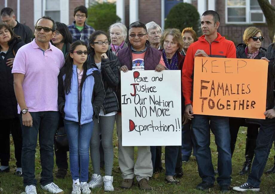 From left, Raphael Benavides and his daughters, Allison, 10, and Brianna, 12, stand with supporters of Miriam Martinez Lemus during a prayer vigil outside the family's home in Stamford on Tuesday. Photo: Matthew Brown / Hearst Connecticut Media / Stamford Advocate