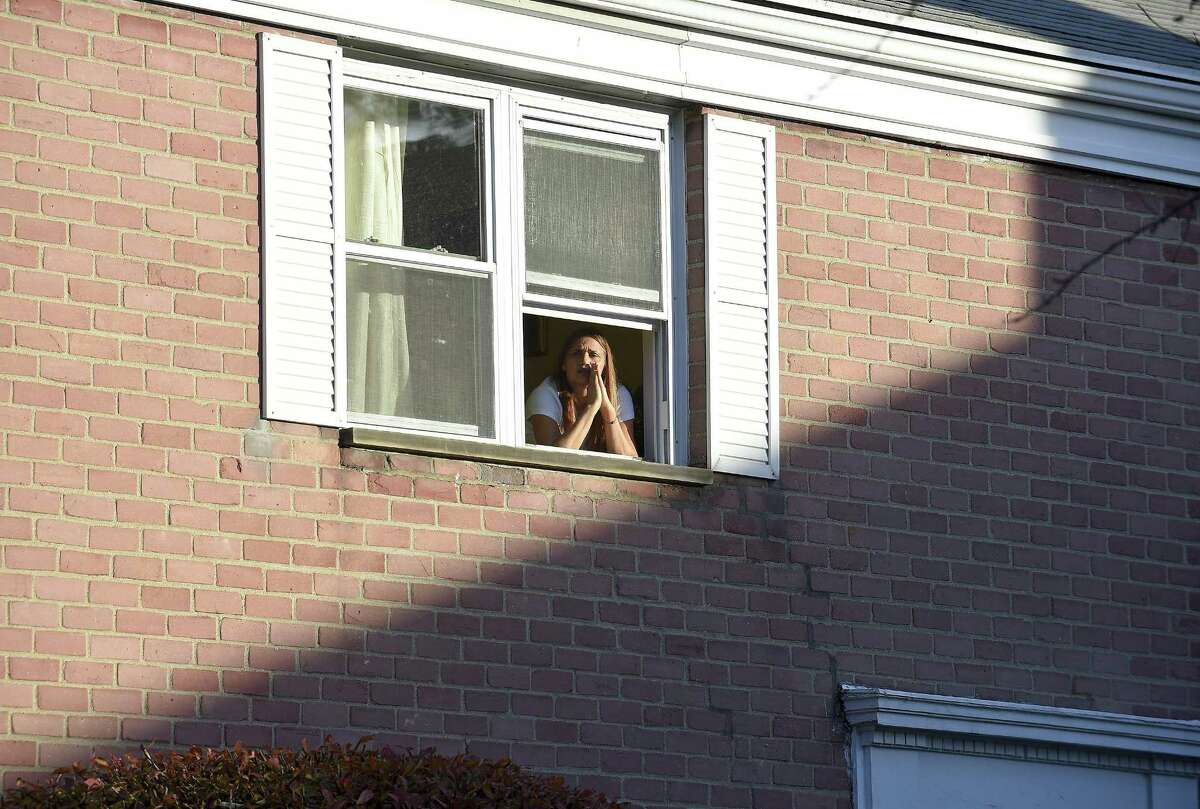 Miriam Martinez Lemus looks out of a window during a prayer vigil this afternoon outside her home in Stamford, Conn. on Tuesday, Nov. 21, 2017.