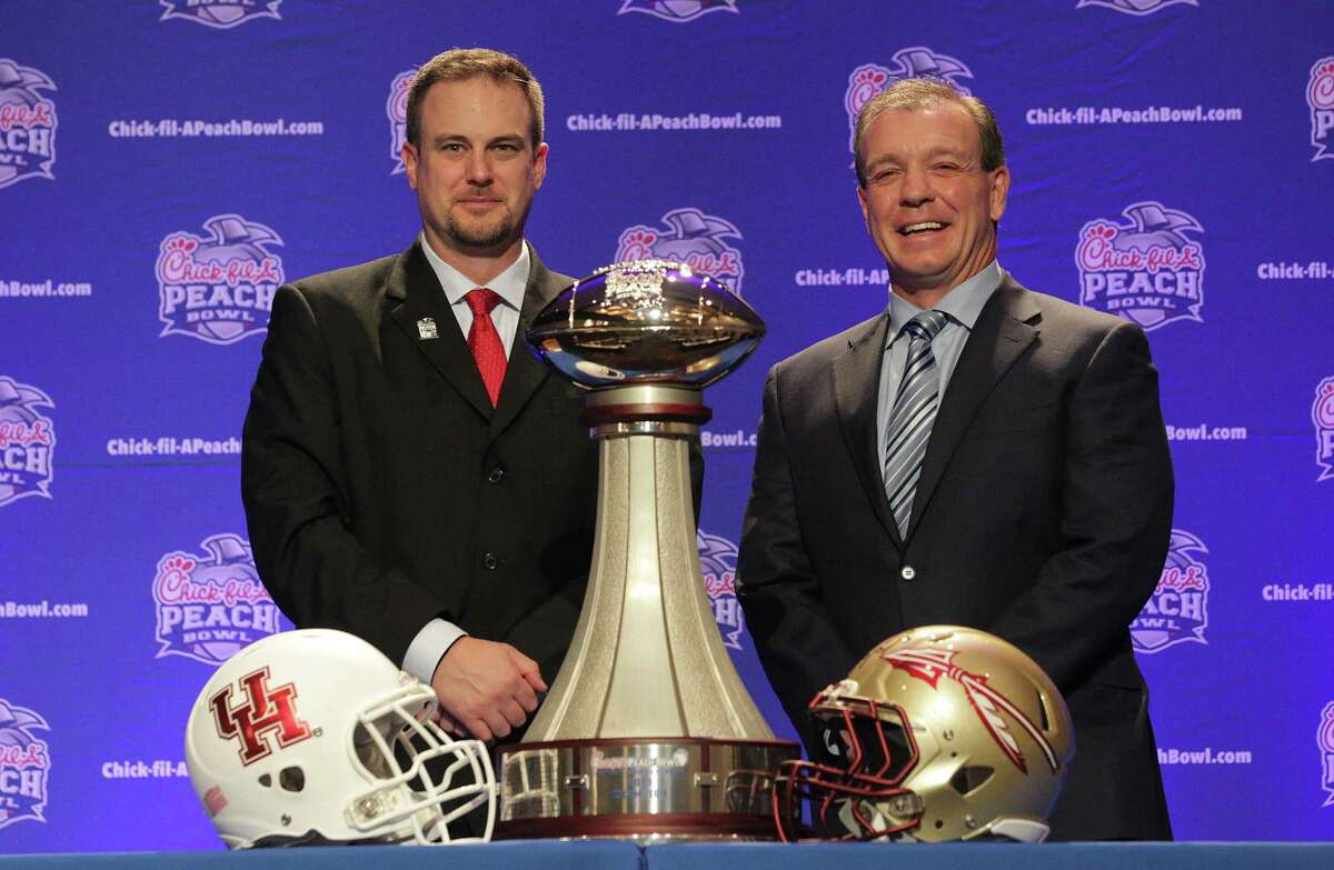 Houston Cougars head coach Tom Herman and Florida State University head coach Jimbo Fisher pose with the Chick-fil-A Peach Bowl trophy on Wednesday, Dec. 30, 2015, in Atlanta. ( Elizabeth Conley / Houston Chronicle )