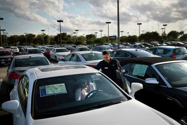 FILE-- A salesman helps customers at a Carmax dealer in Doral, Fla., March 13, 2017. On May 1, automakers reported the fourth straight monthly retreat in sales of new cars and light trucks, the longest stretch of declines since 2009, when the industry was embroiled in crisis and bankruptcies. The slump underscores the view of many that auto sales have peaked and are set to trend downward (Scott McIntyre/The New York Times)