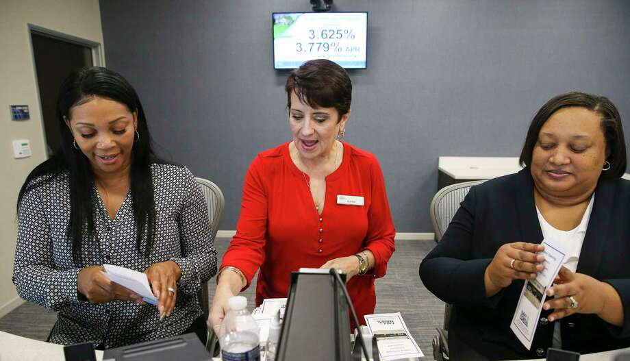 Navy Federal Credit Union branch manager Susan Simmons, center, and tellers Shawntay Hagan, left, and Marie Johnson fold pamphlets as they prepare for their branch's grand opening in Sugar Land.  Photo: Yi-Chin Lee, Houston Chronicle / © 2017 Houston Chronicle