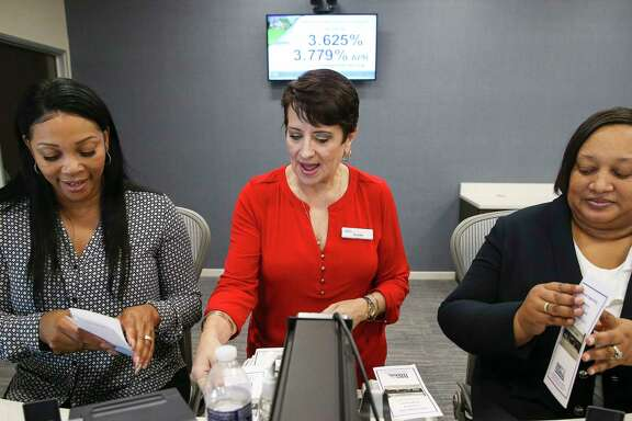 Navy Federal Credit Union branch manager Susan Simmons, center, and tellers Shawntay Hagan, left, and Marie Johnson fold pamphlets as they prepare for their branch's grand opening in Sugar Land.