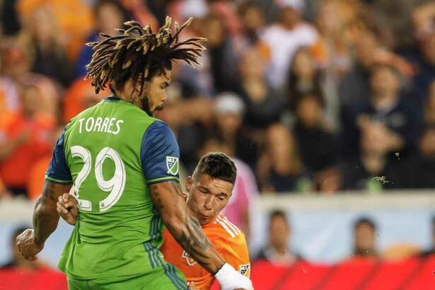 Seattle Sounders defender Roman Torres (29) and Houston Dynamo midfielder Tomas Martinez (25) collide during the first half of the MLS Western Conference Finals at BBVA Compass Stadium on Tuesday, Nov. 21, 2017, in Houston.