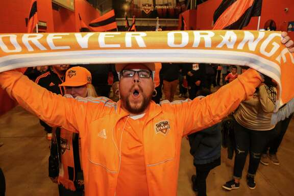 """an El Batallon support group member sings along the Houston Dynamo Goal Song with the band and shows off his """"Forever Orange"""" scarf as they march toward their designated support group area to watch the first leg of the Western Conference Championship between Houston Dynamo and Seattle Sounders FC at BBVA Compass Stadium on Tuesday, Nov. 21, 2017, in Houston. The support group has more than 300 members."""