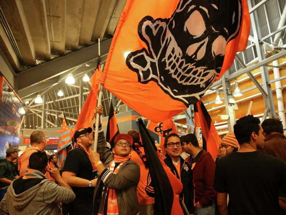 Mannie Gutierrez waves the El Batallon support group flag as they march toward their designated support group area to watch the first leg of the Western Conference Championship between Houston Dynamo and Seattle Sounders FC at BBVA Compass Stadium on Tuesday, Nov. 21, 2017, in Houston. The support group has more than 300 members. Photo: Yi-Chin Lee, Houston Chronicle / © 2017  Houston Chronicle
