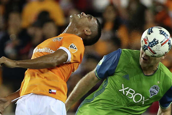Dynamo forward Mauro Manotas, left, is beaten to a header by the Sounders' Chad Marshall,