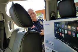 Investigator Joe E. Baeza, Laredo police spokesman, pulls out a television from a Dodge Ram to showcase how people sometimes are victims of a theft when they leave valuables inside their vehicle.