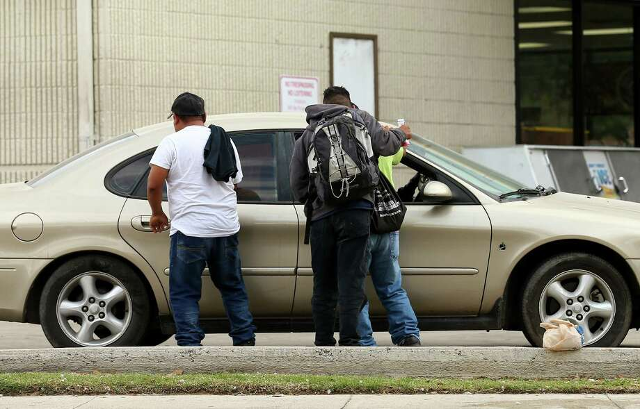 Day laborers approach a vehicle for potential work at a gas station Tuesday, Nov. 21, 2017, in Houston. ( Godofredo A. Vasquez / Houston Chronicle ) Photo: Godofredo A. Vasquez, Houston Chronicle / Godofredo A. Vasquez