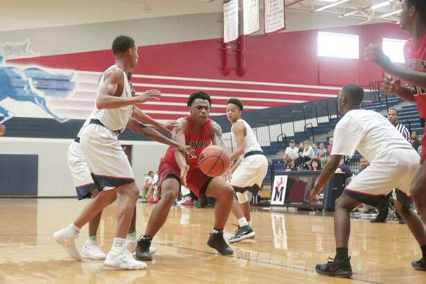 Dawson's Kyle Matthews tries to come up with a loose ball in a non-district boys' basketball game Tuesday against Manvel.